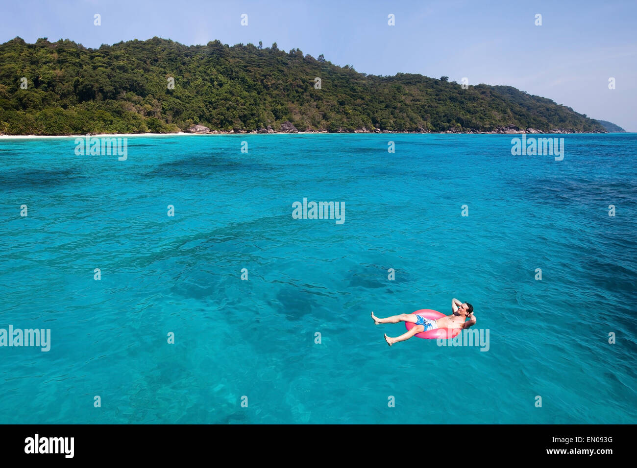 travel insurance concept, man swimming in lifebuoy on paradise beach - Stock Image