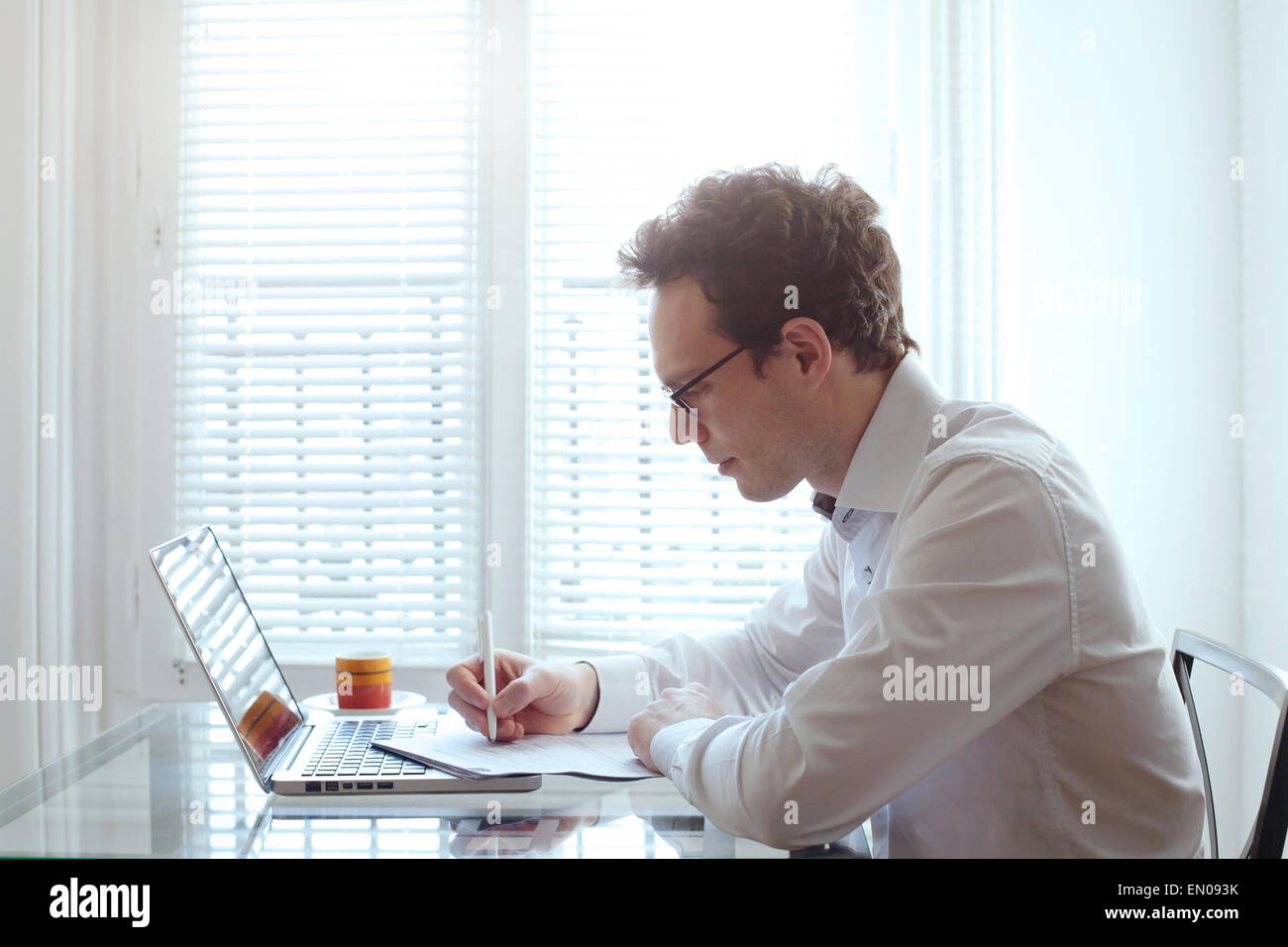 young business man working with documents and laptop in bright office interior - Stock Image