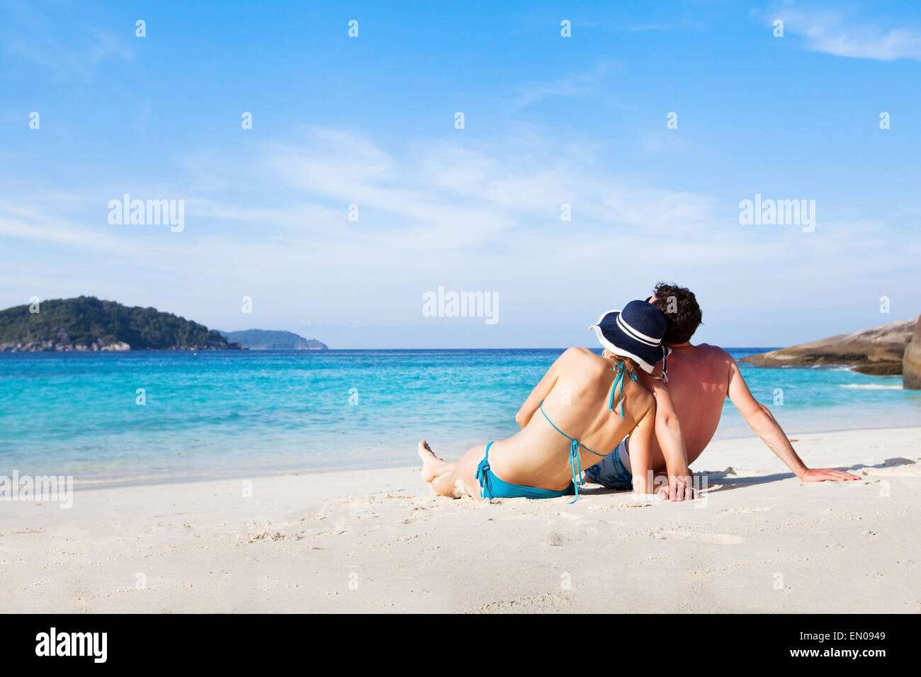 couple sitting and relaxing on the paradise beach during their honeymoon Stock Photo