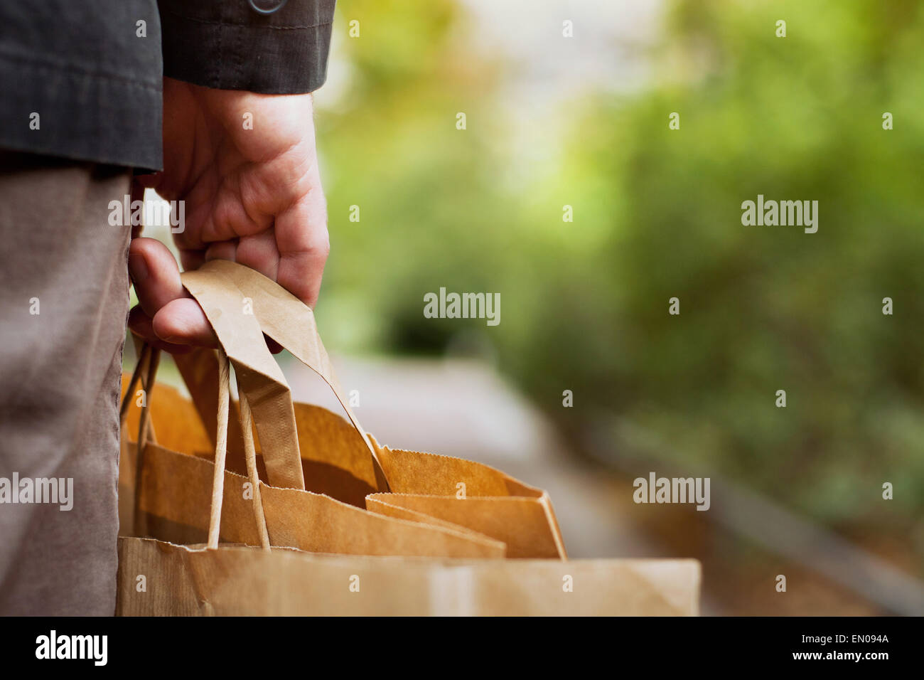 consumer basket, close up of paper shopping bags in male hand - Stock Image