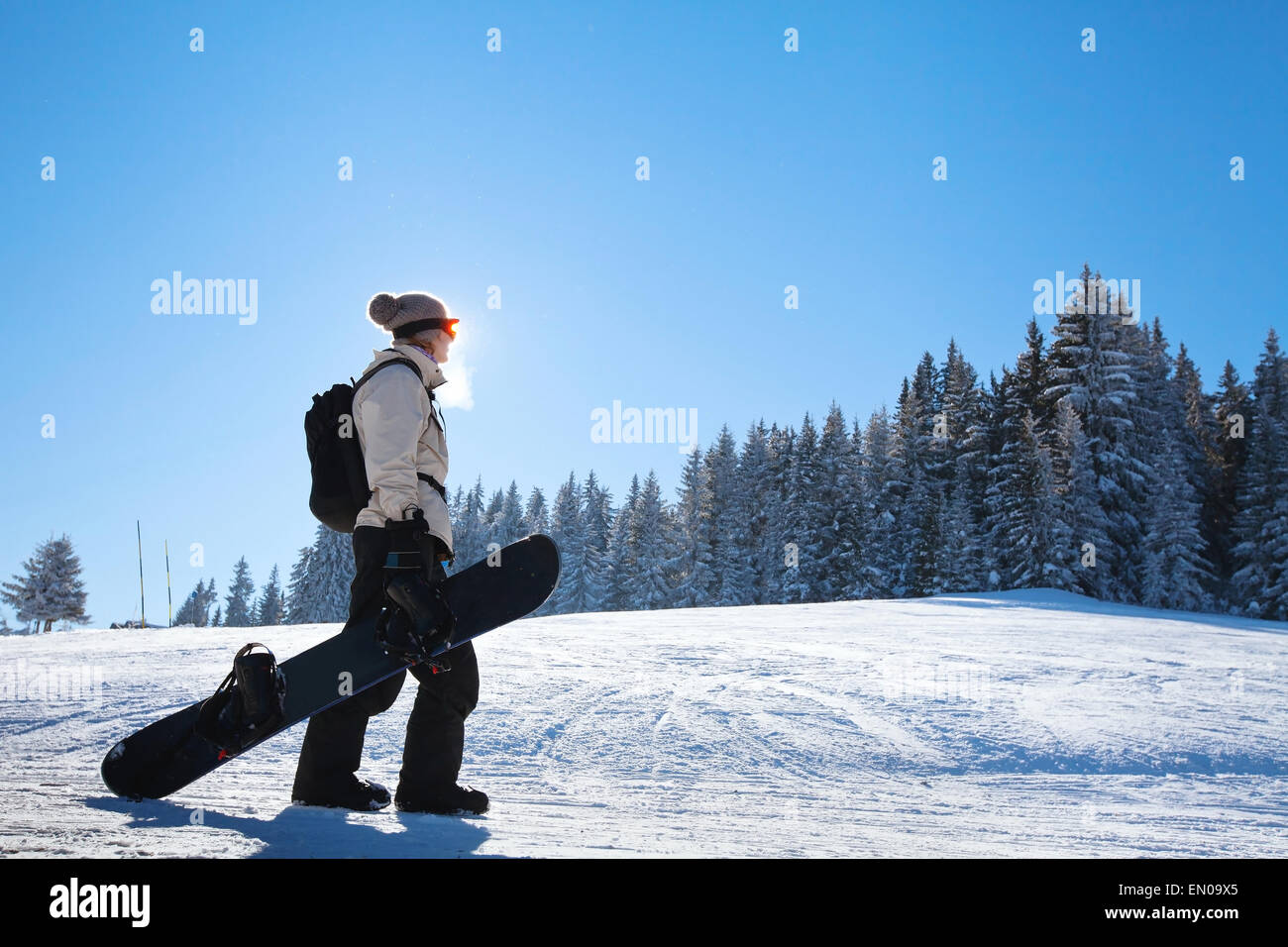 silhouette of woman with snowboard on the ski slope - Stock Image