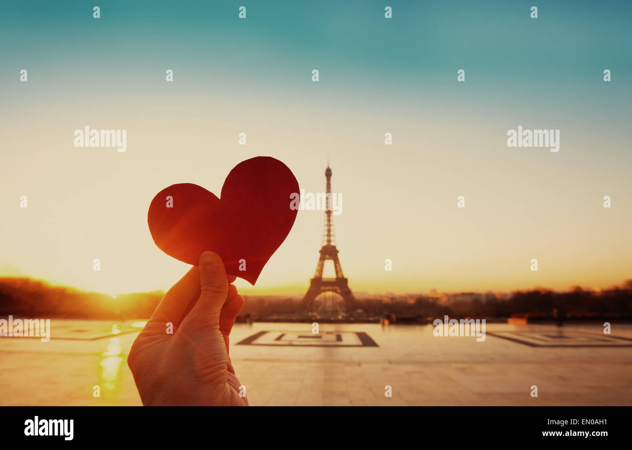 beautiful vintage card from Paris, Eiffel tower and hand with paper heart at sunrise Stock Photo