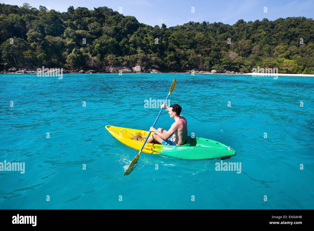 young caucasian man on kayak near paradise island in turquoise water - Stock Image
