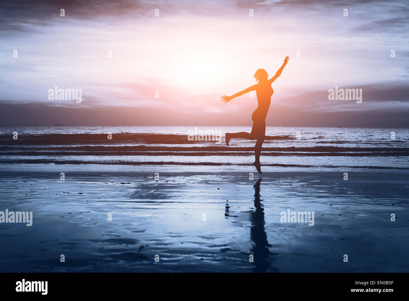 healthy life, silhouette of carefree woman on the beach - Stock Image