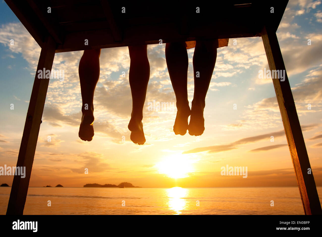 silhouette of feet of couple sitting on the pier at sunset beach, low angle view - Stock Image