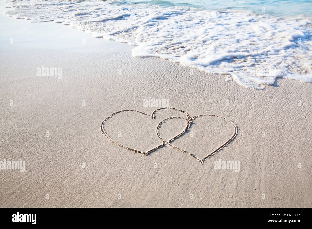 two hearts drawn on perfectly white sand of paradise beach - Stock Image