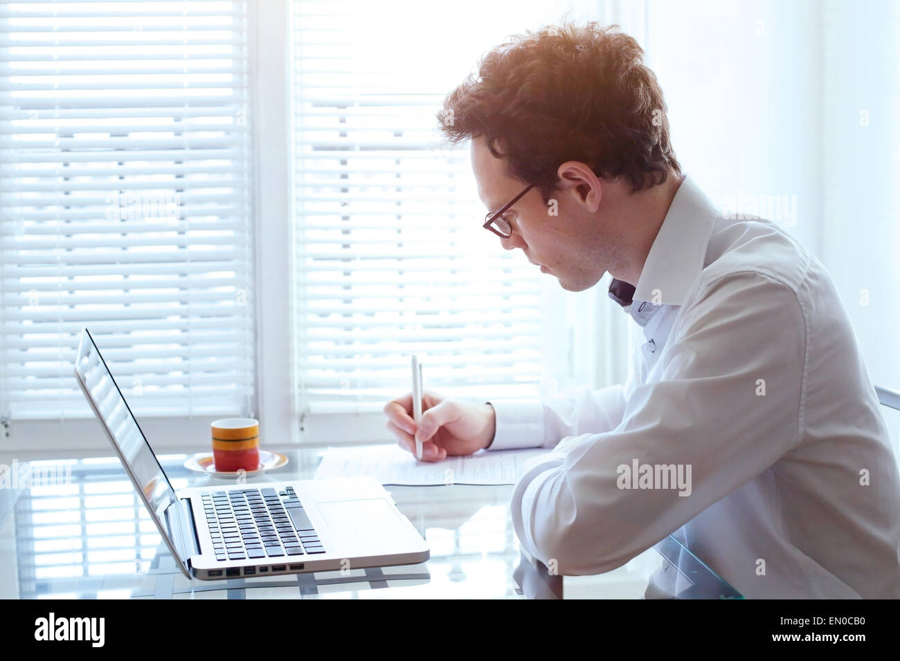 writing resume, young handsome business man working in office - Stock Image