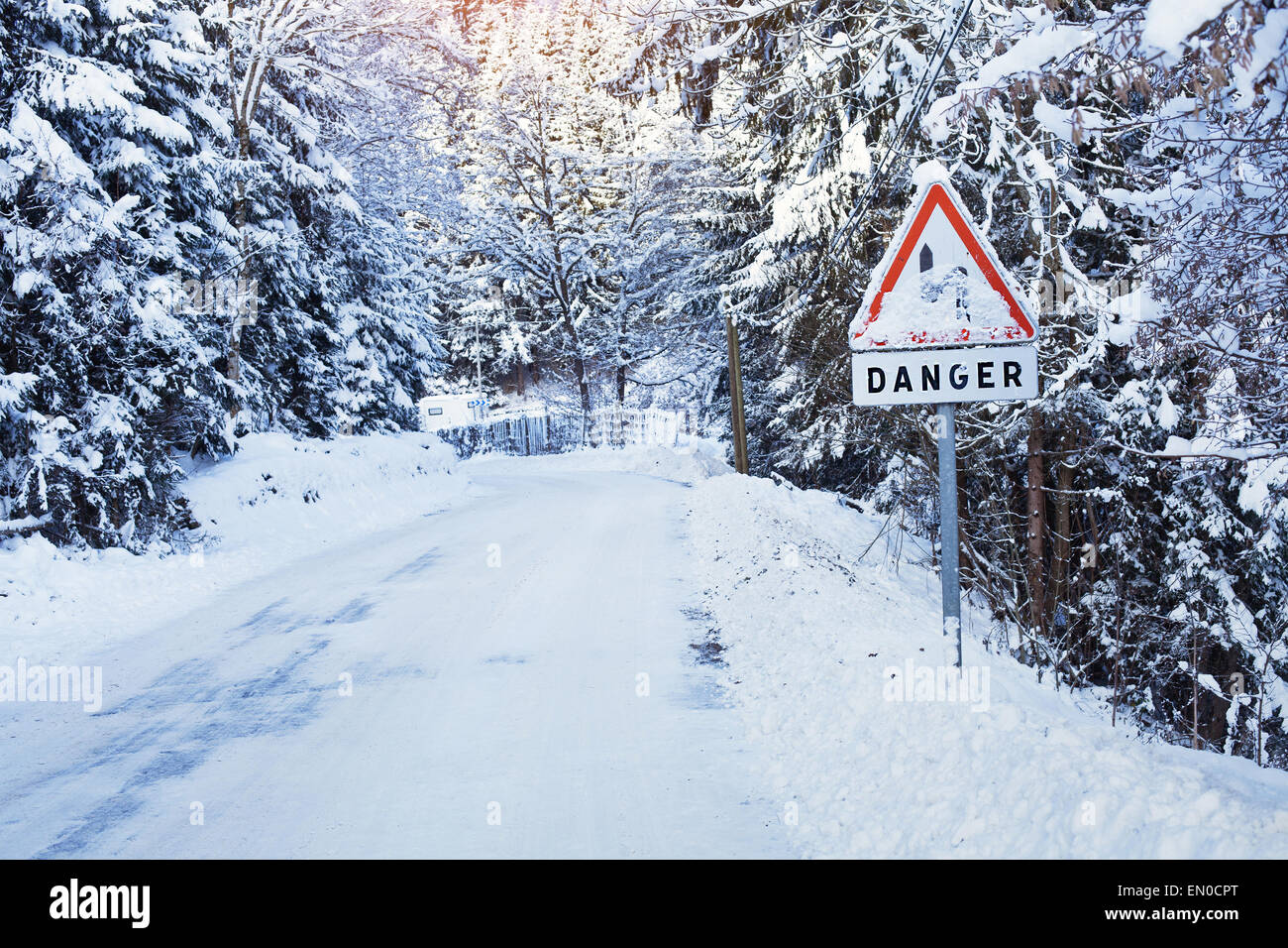danger sign on the frozen road - Stock Image