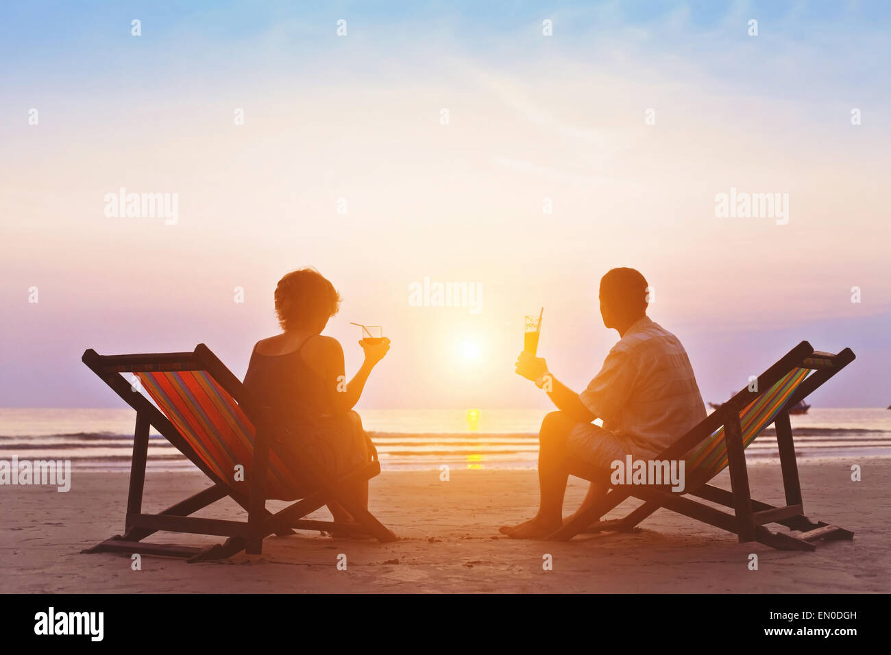 family enjoying romantic sunset on the beach - Stock Image