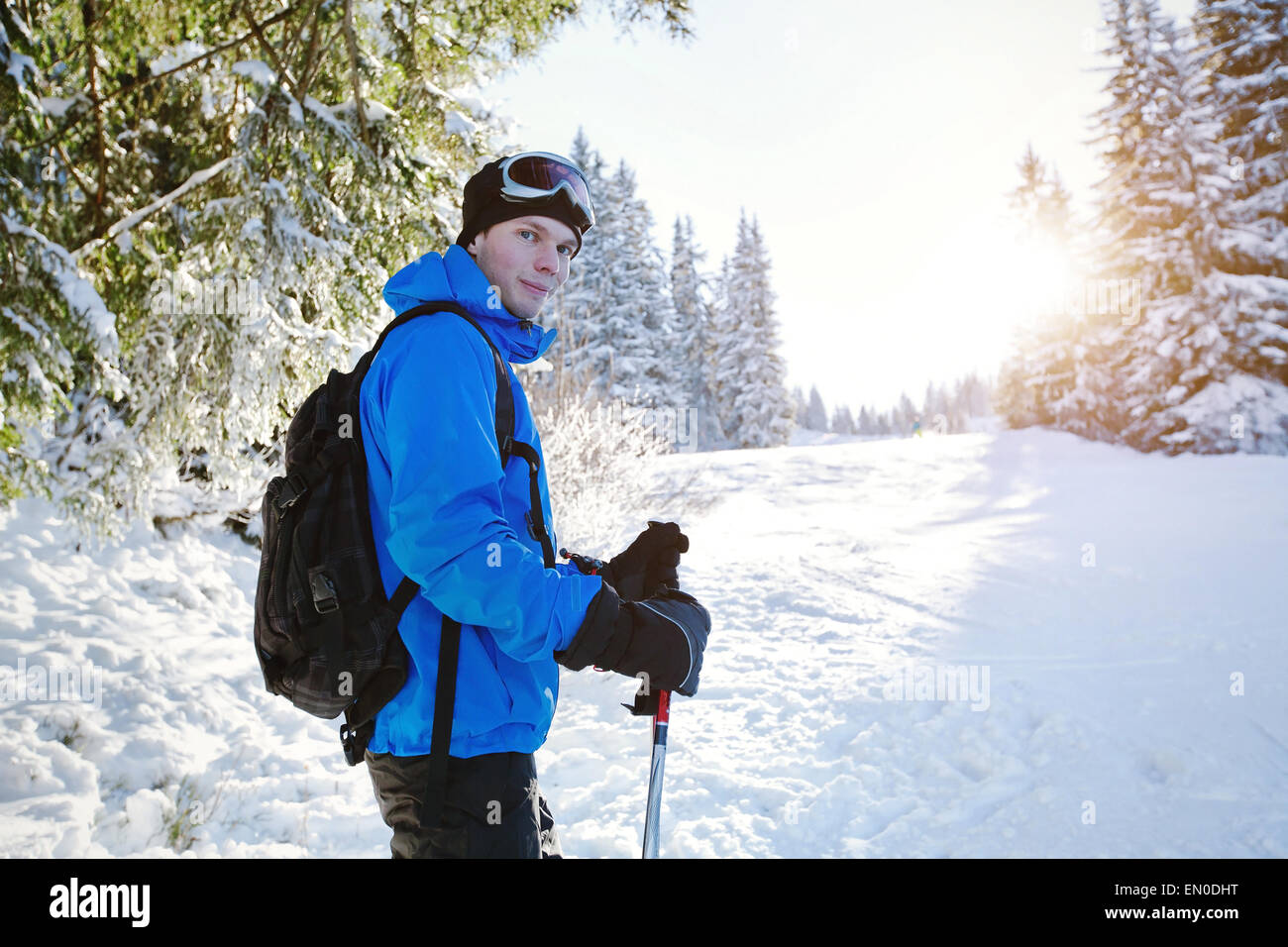 portrait of young handsome skier in winter forest - Stock Image