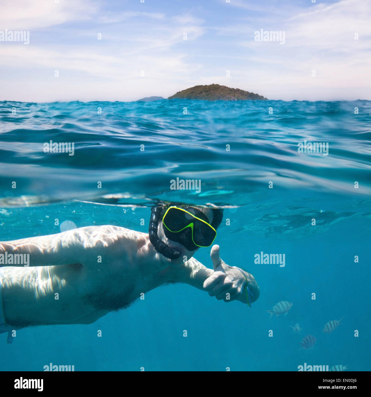 young man snorkeling, underwater split photo - Stock Image