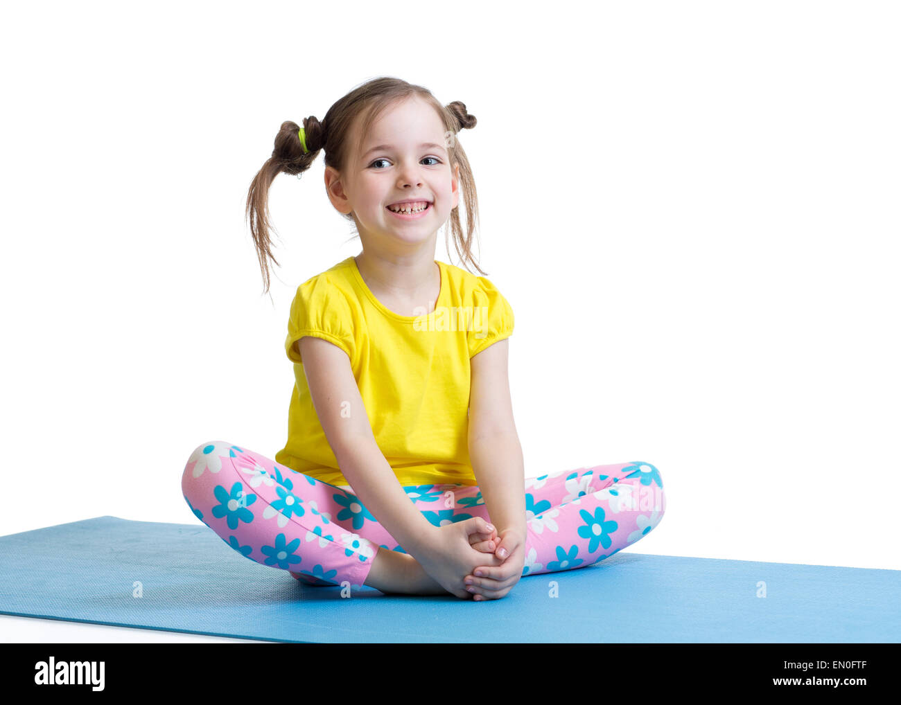 child girl does gymnastics sitting in butterfly pose isolated on white - Stock Image
