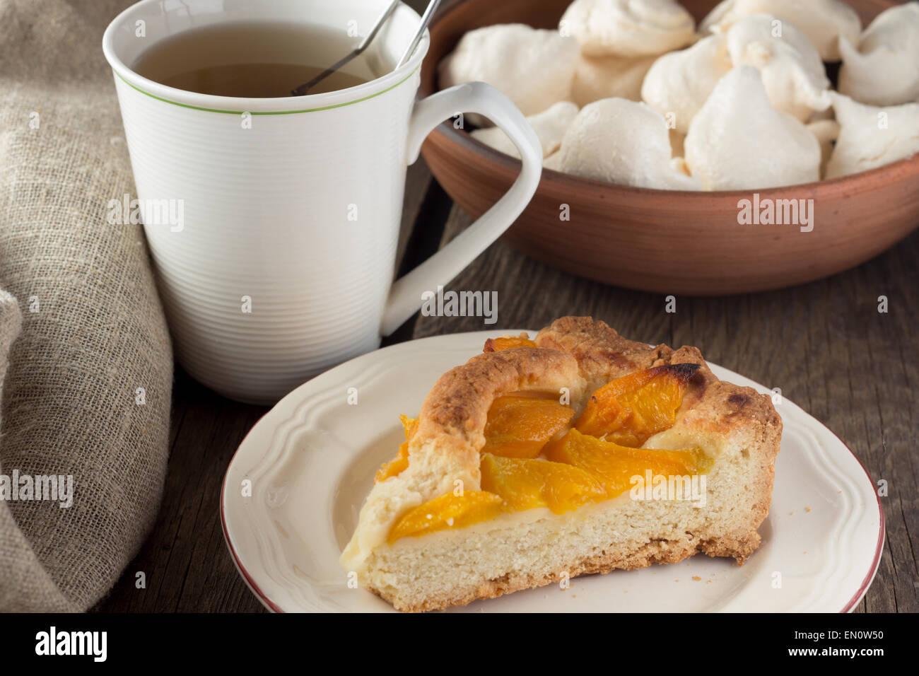Shortcrust peach pie and cup of tea selective focus horizontal - Stock Image
