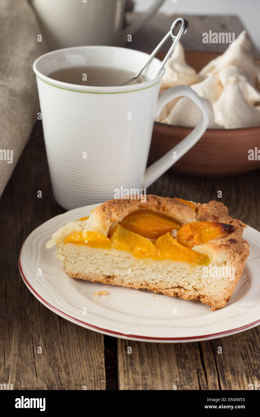 Shortcrust peach pie and cup of tea selective focus vertical - Stock Image