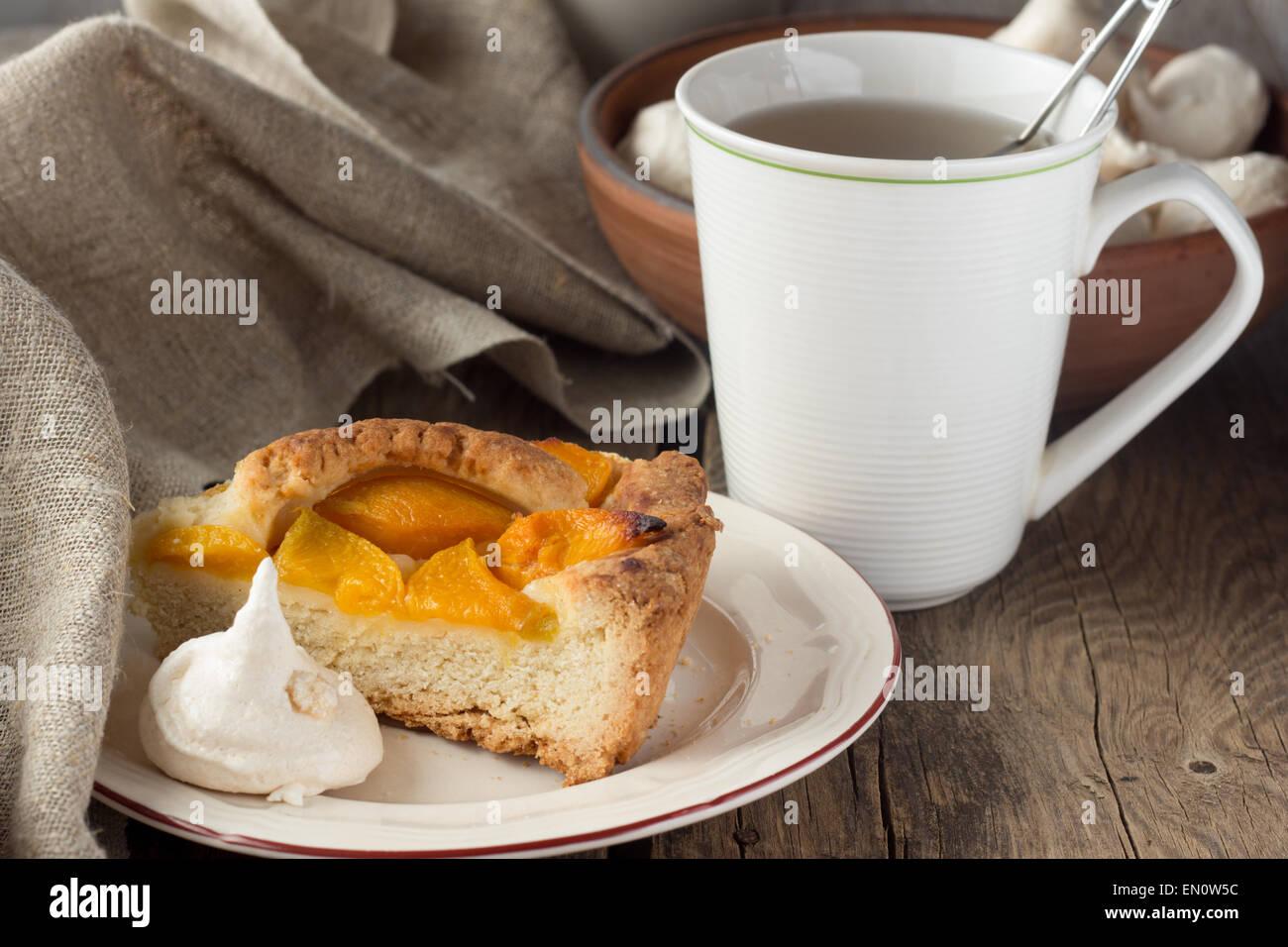 Shortcrust peach pie, meringue and cup of tea selective focus horizontal - Stock Image