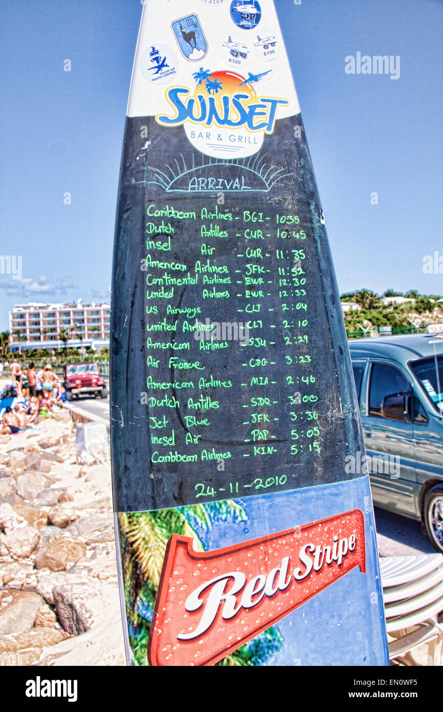 Maho Beach on the Island of St. Marten Flight Times written in green Chalk on a blackboard made from a Surf Boad - Stock Image