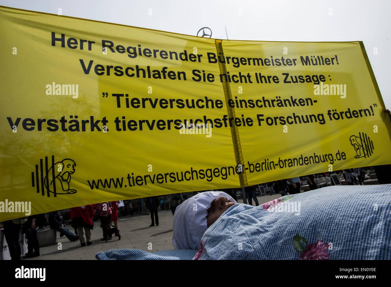 A doll lies in a bed in front of a banner that reads 'Herr Regierender Buergermeister Mueller! Verschlafen Sie - Stock Image