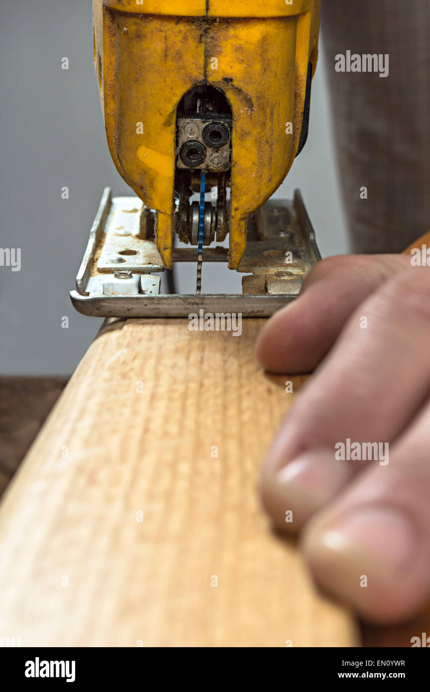 Woodworker cutting a piece of wood using a electric jigsaw - Stock Image