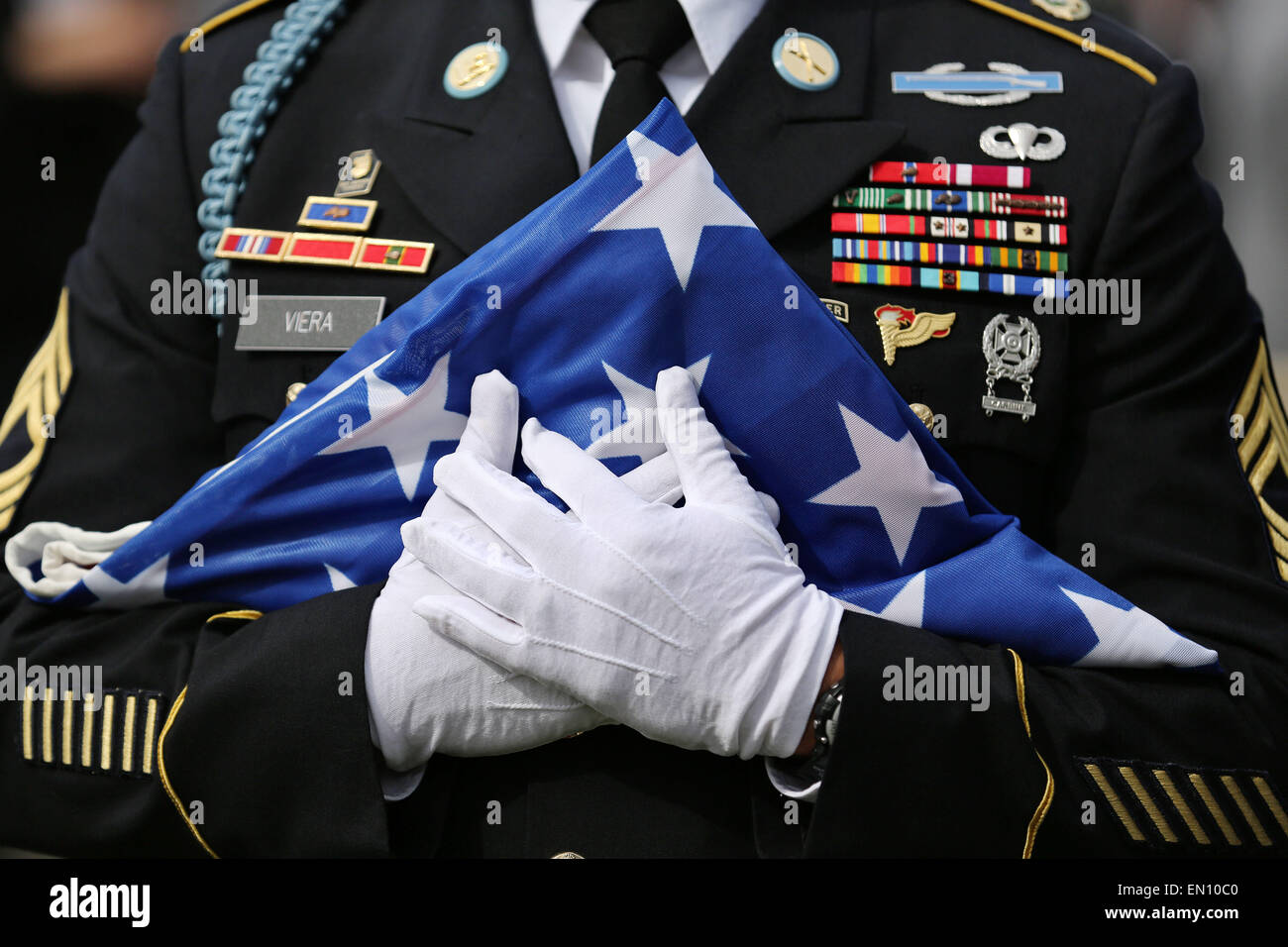 Torgau, Germany. 25th Apr, 2015. A US soldier holds a folded flag of the United States during a ceremony entitled Stock Photo