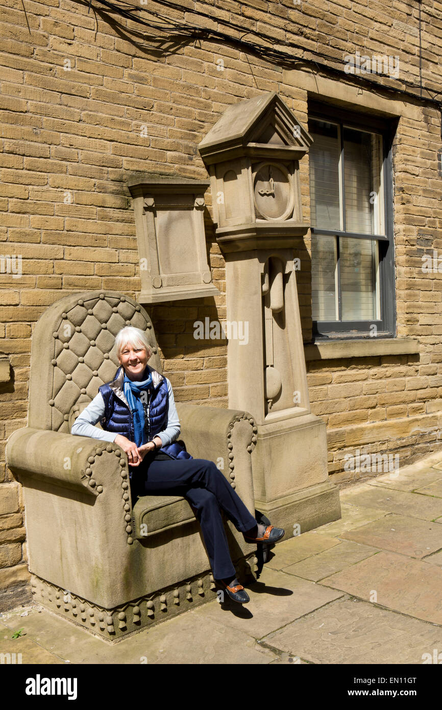 UK, England, Yorkshire, Bradford, Little Germany, woman sat on grandad's clock and chair sculpture by Timothy Shutter - Stock Image