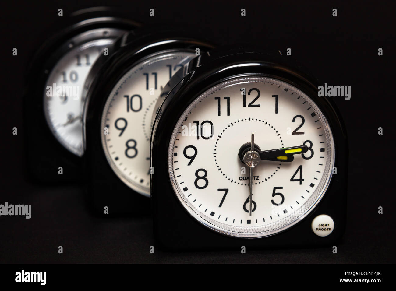 Three alarm clocks one behind the other - Stock Image