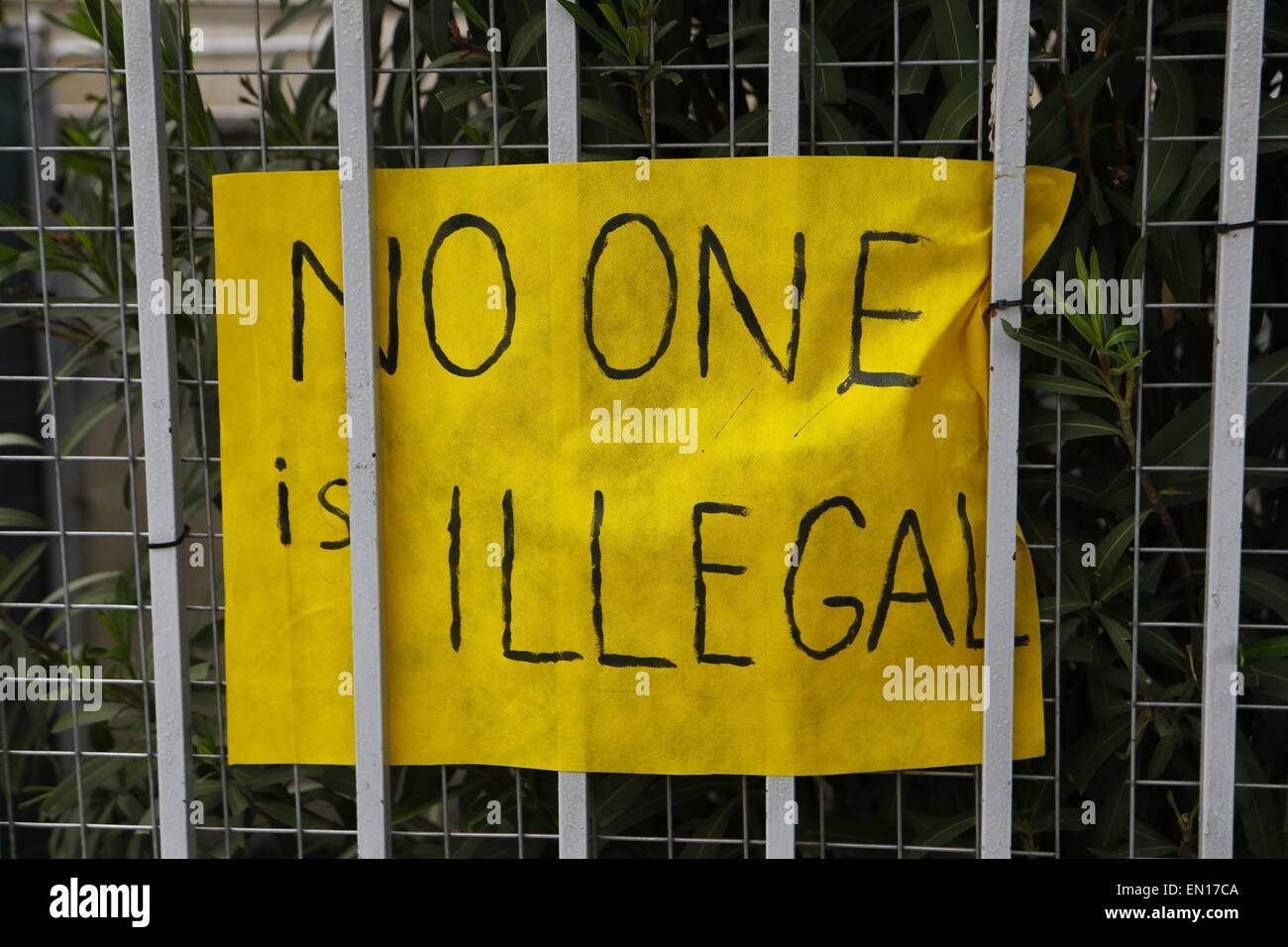 Athens, Greece. 25th Apr, 2015. A sign that reads 'No one is illegal' hangs on the fence of the Ministry. - Stock Image