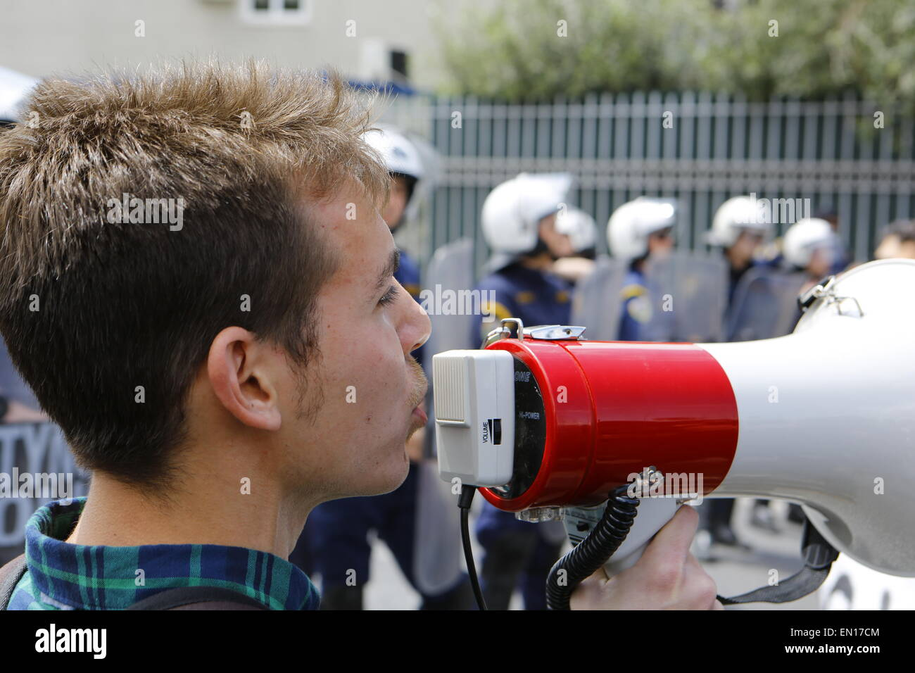 Athens, Greece. 25th Apr, 2015. A protester shouts slogans through a megaphone. Riot police officers can be seen - Stock Image