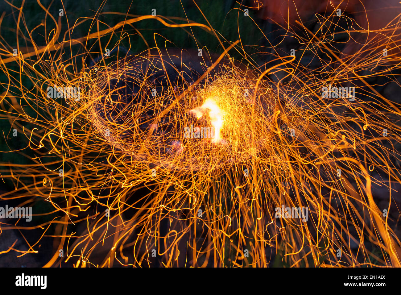 Long exposure of sparks flying off a barbecue fire. - Stock Image