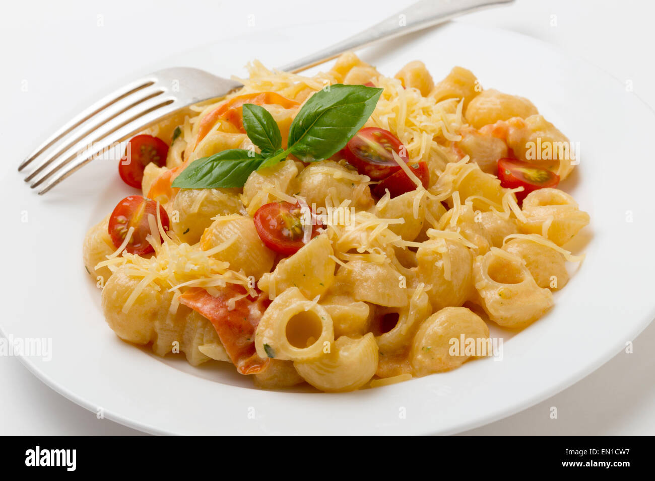 Gomiti rigata 'elbow' pasta tossed with tomatoes cooked in cream with green pesto, cherry tomatoes and grated - Stock Image
