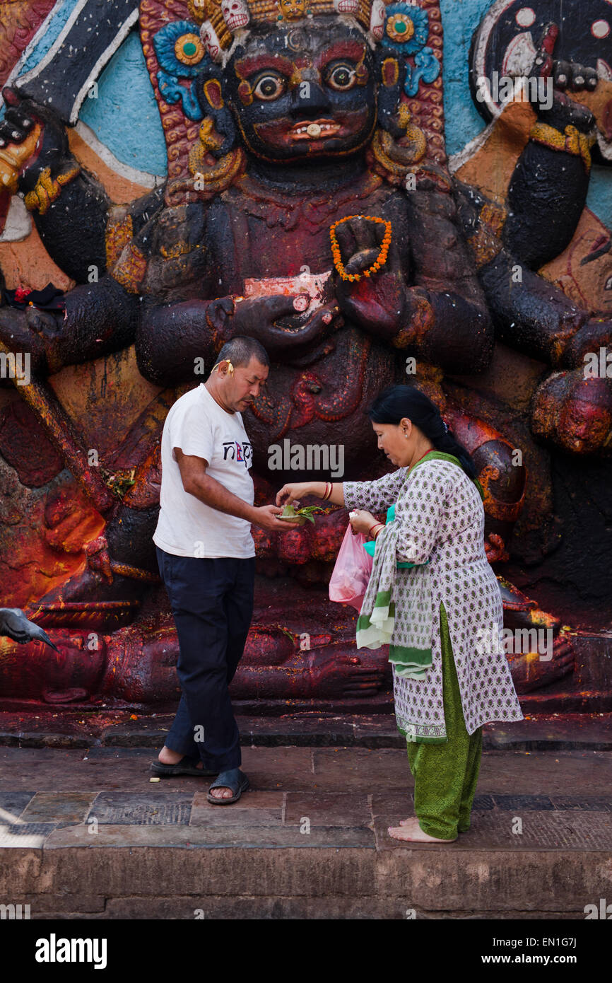 Woman offering to lord Shiva in Durbar Square - Stock Image