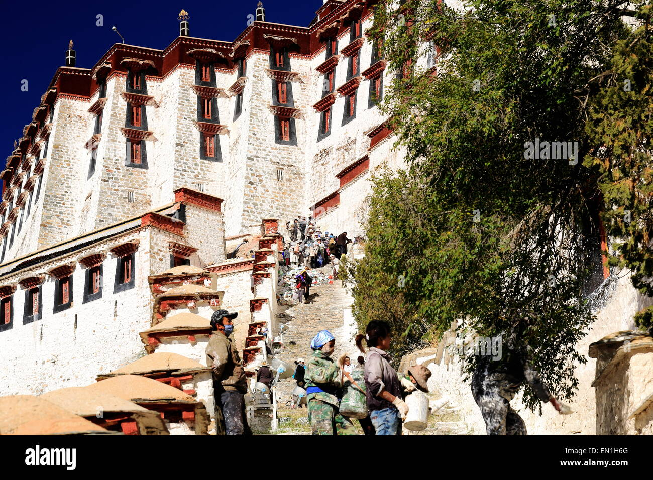 LHASA, TIBET, CHINA-OCTOBER 20: Tibetan workers whitewash the walls in the Potala palace while some locals get to - Stock Image