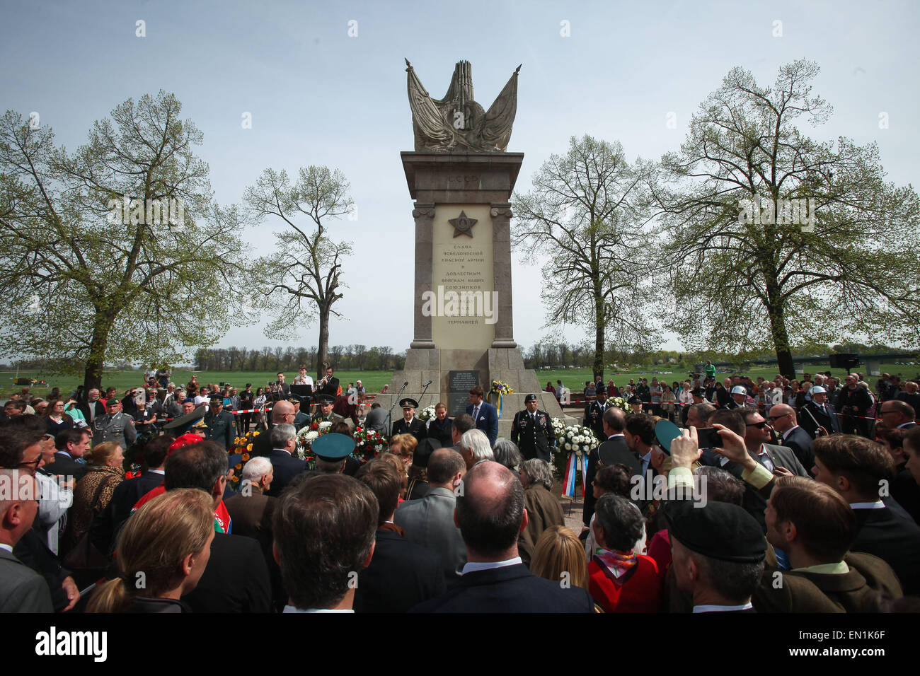 Torgau, Germany. 25th Apr, 2015. Visitors put a flower wreath in front a monument during celebrations of the 70th Stock Photo