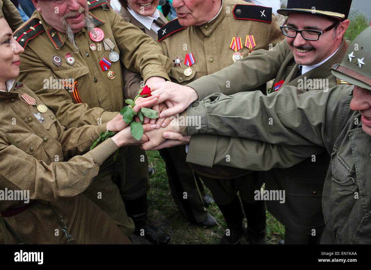 Torgau, Germany. 25th Apr, 2015. Amateur actors wearing military uniforms of allied forces hold a rose together Stock Photo