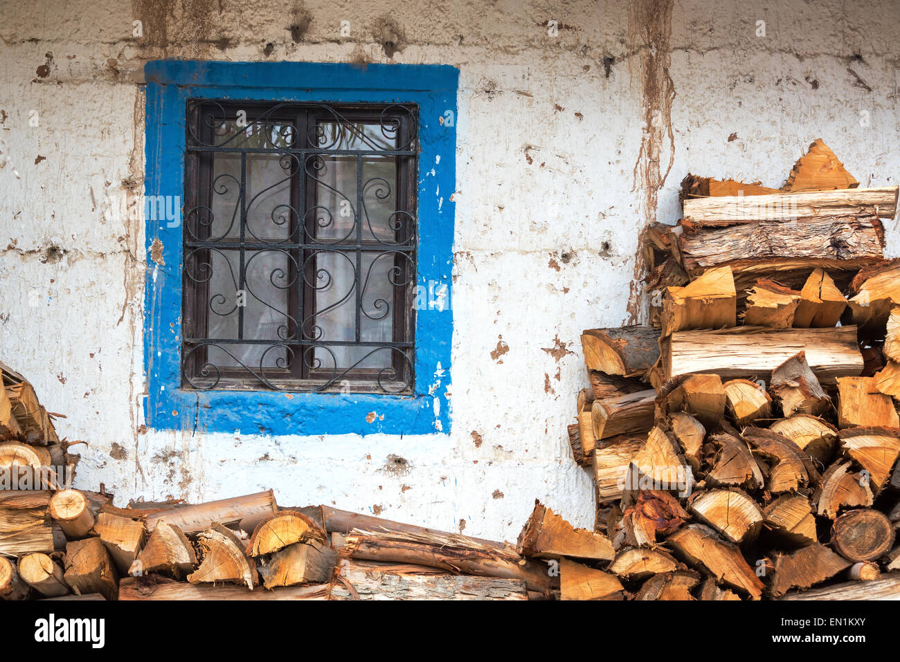 Firewood next to a blue and white colonial window in Tarma, Peru - Stock Image