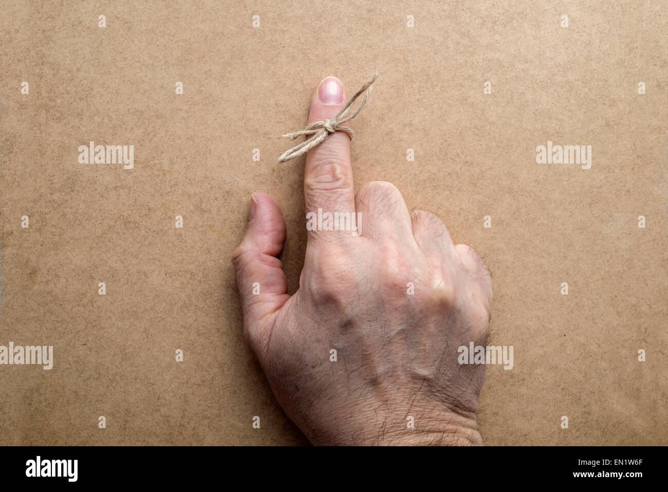 String on index finger of an elderly man. Wooden background - Stock Image