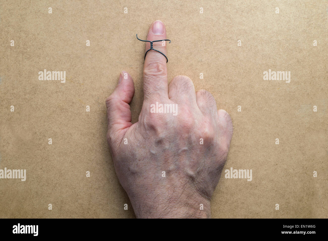 Wire on index finger of an elderly man. Wooden background - Stock Image