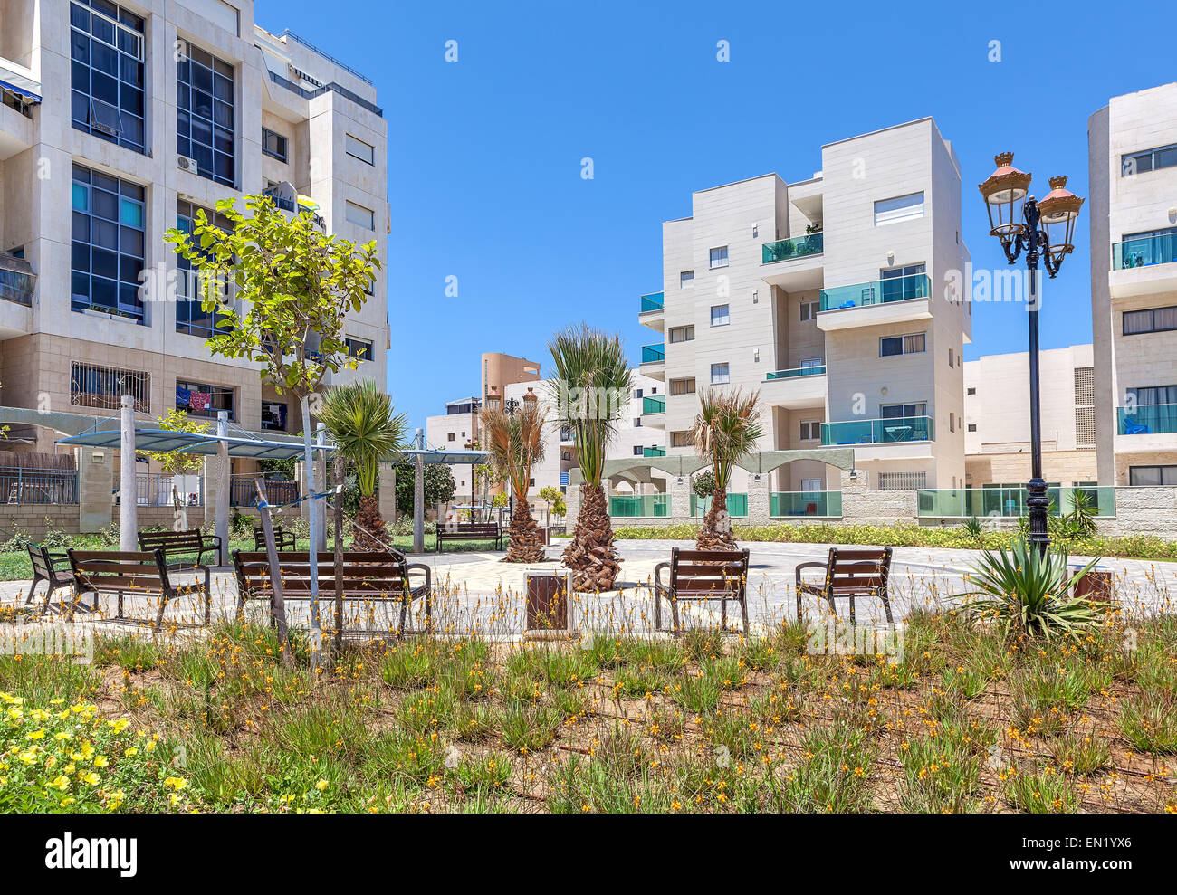 Small city square with palms and benches near complex of contemporary residential buildings in Ashqelon, Israel. - Stock Image