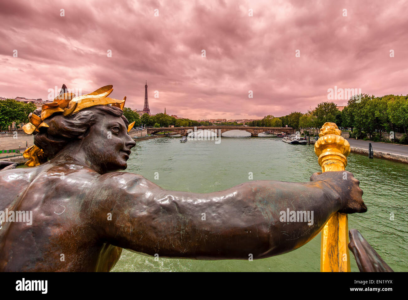View of Seine river and Eiffel Tower on background under cloudy sky from Alexander the III bridge in Paris, France. - Stock Image