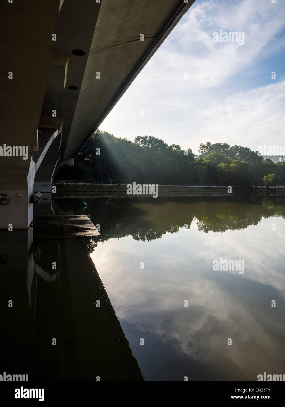 Reflections of trees and clouds on a lake, viewed from under a bridge - Stock Image