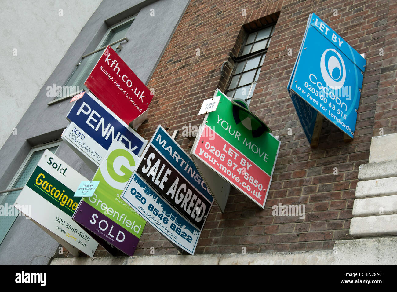 cluster of estate agents signs, for sales and lettings, on a building in kingston upon thames, surrey, england - Stock Image
