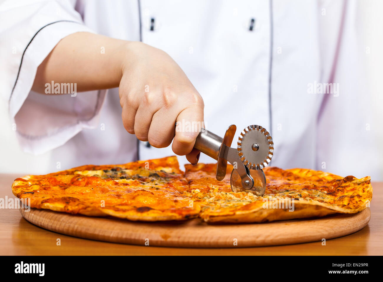 chef with knife cuts the pizza closeup - Stock Image