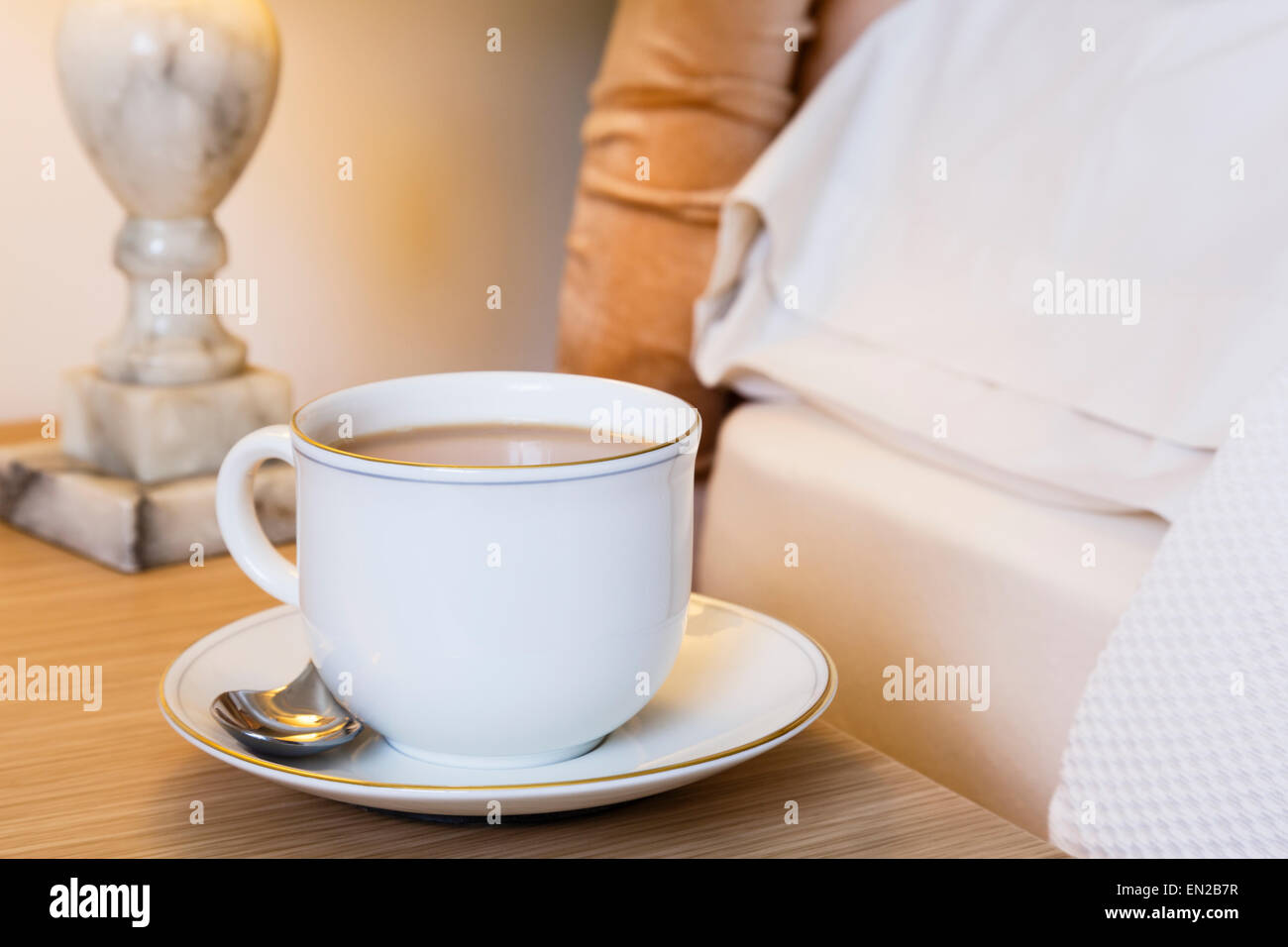 Morning cup of English tea on a bedside table at side of a bed. Everyday lifestyle. England UK Britain - Stock Image