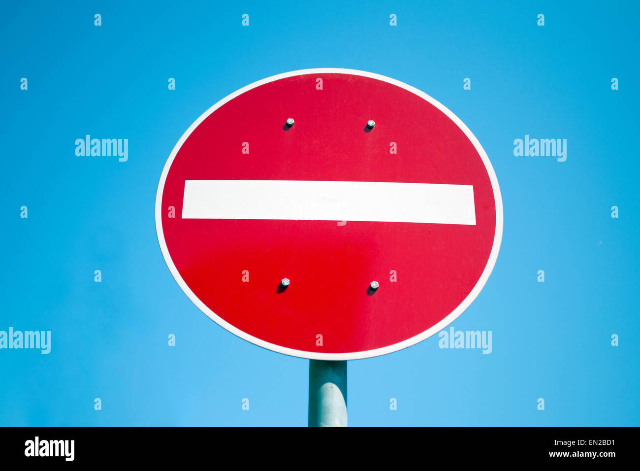 Red and white no entry road sign against blue sky Stock Photo