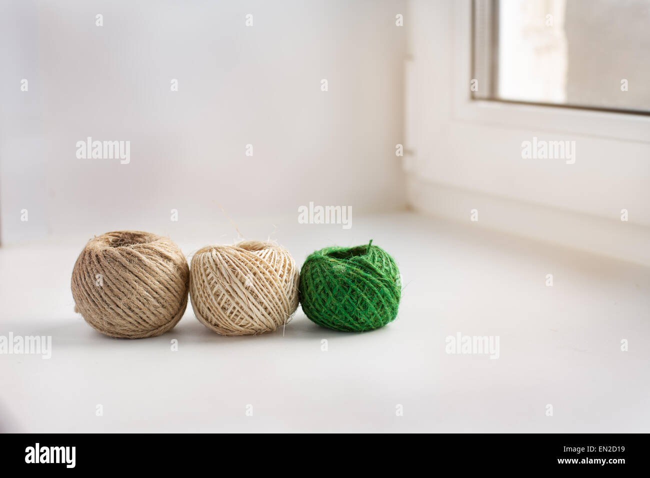 Three skeins of thread in a row on the windowsill - Stock Image