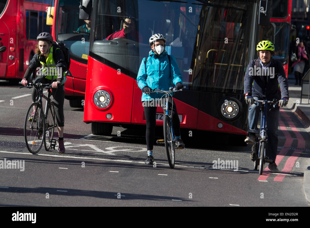 London cyclists at traffic lights during morning rush hour, with cyclist wearing anti pollution mask - Stock Image