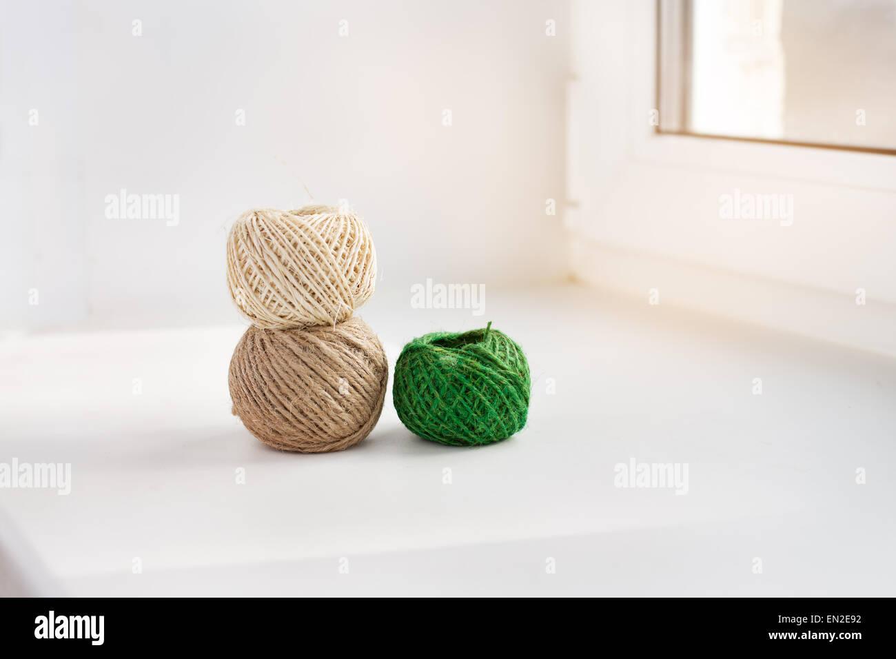 Three skeins of thread on the windowsill - Stock Image