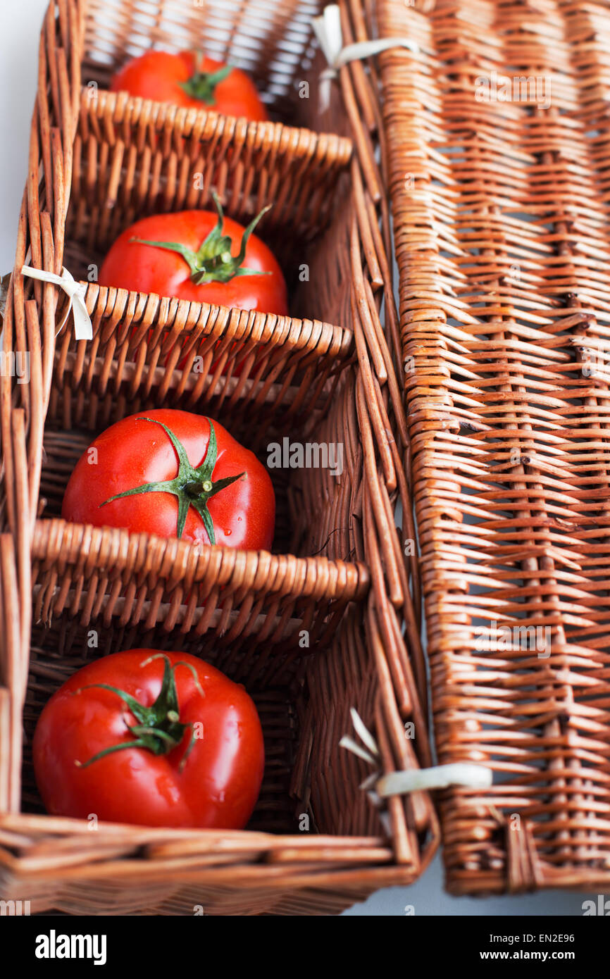 Four tomatoes lying separately in wicker box - Stock Image