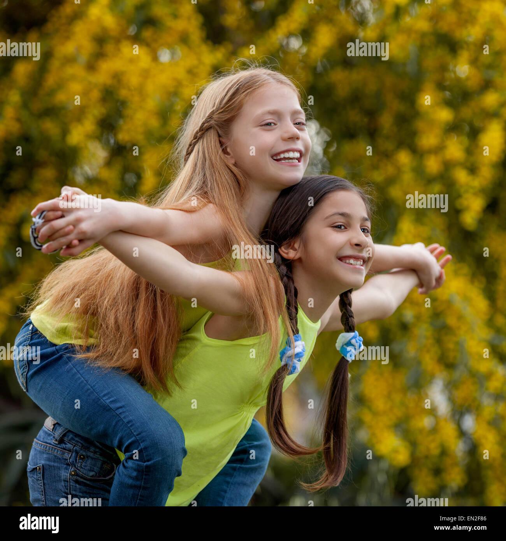 piggyback  happy healthy smiling summer kids - Stock Image