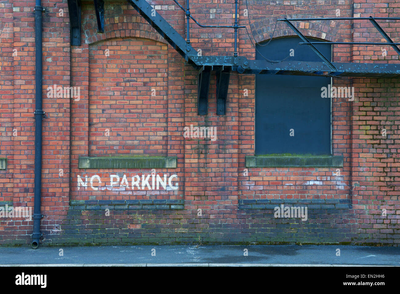 No parking sign on industrial brickwork building, - Stock Image