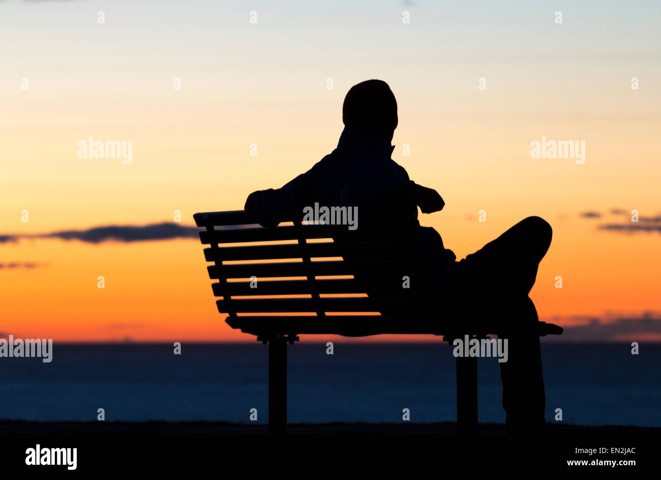 Depression, loneliness... concept image. Silhouette of man sitting alone on seat overlooking sea at sunset. - Stock Image